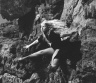 André De Dienes / Model in net stockings posing on rocks (at shore?) / ca 1950s