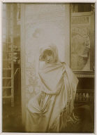 Model Draped in a Shawl posed against Mucha posters