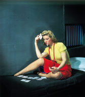 Woman in cell, playing solitaire