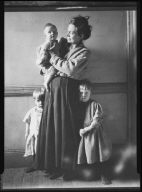 Woman Holding Child, Two Children Nearby