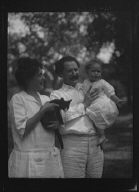 Nadelman, Mr. and Mrs., with baby and cat, standing outdoors