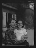 Churchill, Mrs., with child Orrin, seated outdoors