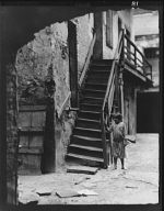 Child standing next to a stairway in a courtyard, New Orleans