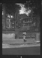 Child walking past a gate, New Orleans or Charleston, South Carolina