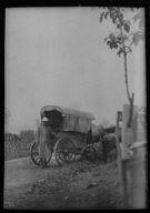 Man standing behind a horse-drawn wagon, Japan