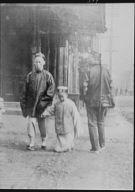 Man smoking a cigar crossing a street with a boy, Chinatown, San Francisco