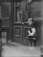 Small boy standing in front of a door, Chinatown, San Francisco