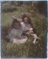 Two girls wearing white dresses and bows, one holding a doll, seated in the garden of Genthe's studio in San Francisco