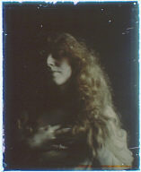 Head and shoulder of a woman with long red-brown hair with one hand on her chest