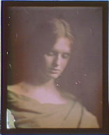Head and shoulders of a woman in yellow or gold