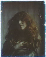 Head and shoulders of a woman with long red-brown hair with one hand on her chest