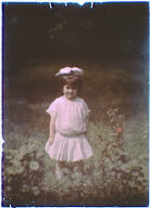 Girl wearing a white dress and a bow in her hair standing in a garden