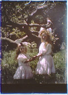 Two girls wearing white dresses with bows in their hair standing in the garden of Genthe's studio in San Francisco