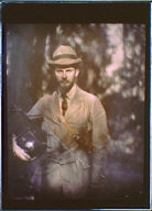 Alvin Langdon Coburn standing in woods holding a camera