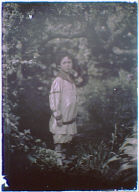Boy, possibly a son of Morley Kennerley, standing in a garden