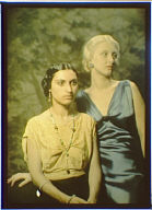 Two women, one dressed in yellow and one in blue