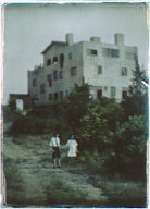 Boy and girl standing on a dirt road leading to a three-story house