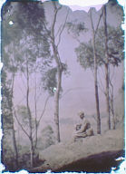 Alvin Langdon Coburn seated on a hill holding a camera