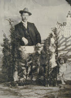 Studio Portrait in front of Cliff House [man in hat behind fence and shrubbery]