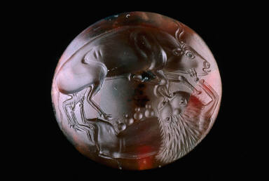 Lens-shaped sealstone with lioness attacking a bull