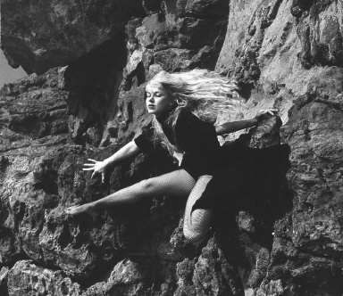 Model in net stockings posing on rocks (at shore?)