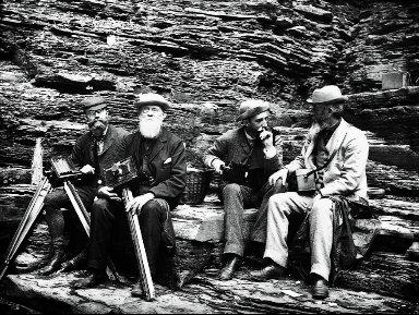 Four photographers group in parlor at Enfield Glen, 1885