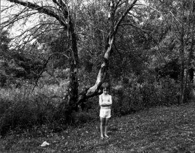 Child by dead tree