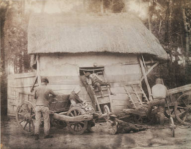 Peasant family at rest in front of a thatched shed
