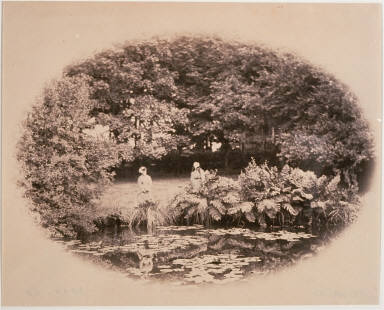 Women sitting by small pond