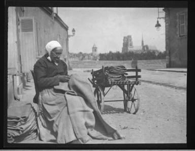 Old Woman Mending Bags In View Of The Cathedral Of Orleans France