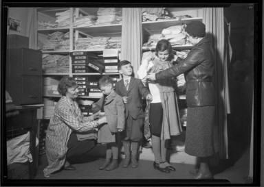 Two Women Help Children Dress