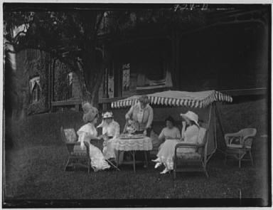 Group of women seated outdoors having tea