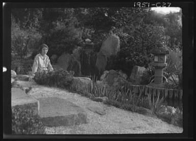 Unidentified woman seated in a garden next to a stream, possibly belonging to A.W. Bahr