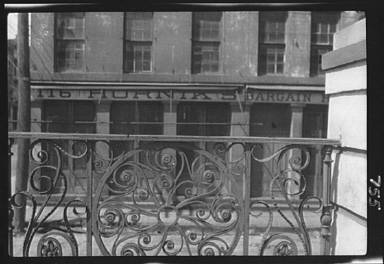 Facade of a building seen through the wrought iron railing of the Market Hall, Charleston, South Carolina