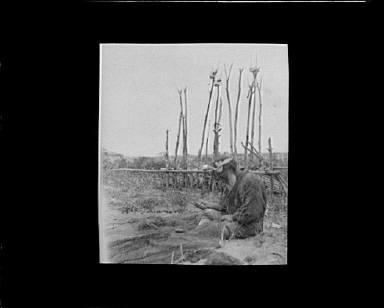 Ainu man seated outside working on nets