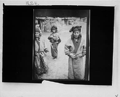 Three Ainu women outside in the village lane