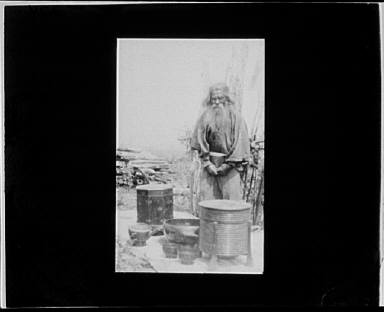 Ainu man standing outdoors on a mat covered with clay containers