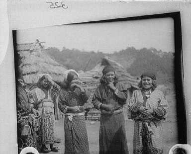 Ainu woman standing outside in the middle of village