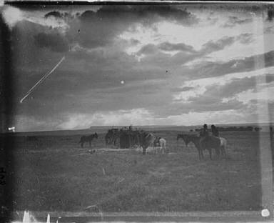 Horses and riders with a mesa in the background