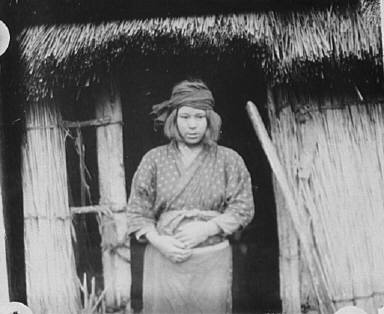 Ainu woman standing by the doorway of a hut