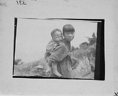Japanese or Ainu girl carrying a child