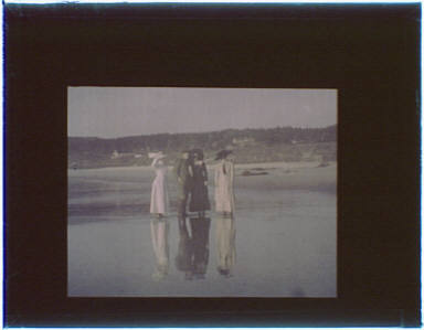 Three women and one man standing on the beach in the Carmel, California area