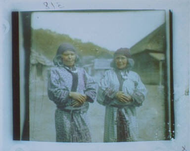 Ainu women standing outside in the middle of village