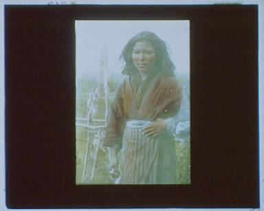 Ainu woman standing outside in front of a pole fence