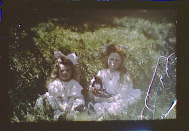 Two girls wearing white dresses and bows seated in the garden of Genthe's studio in San Francisco