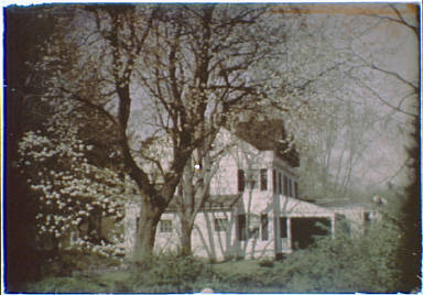 Side view of a two-story house with white planking and blsck shutters and a porch