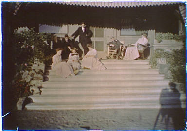 Group of people sitting on the steps and porch of a house, including, possibly, John Henry Patterson