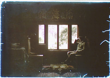 Arnold Genthe seated by the window of his bungalow in Carmel, California