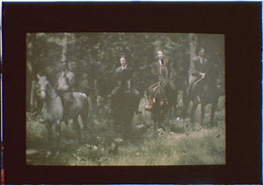 Four men on horseback in a wooded area