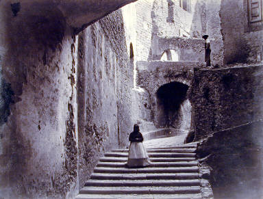 Northern Italy [woman coming down steps, series of archways]